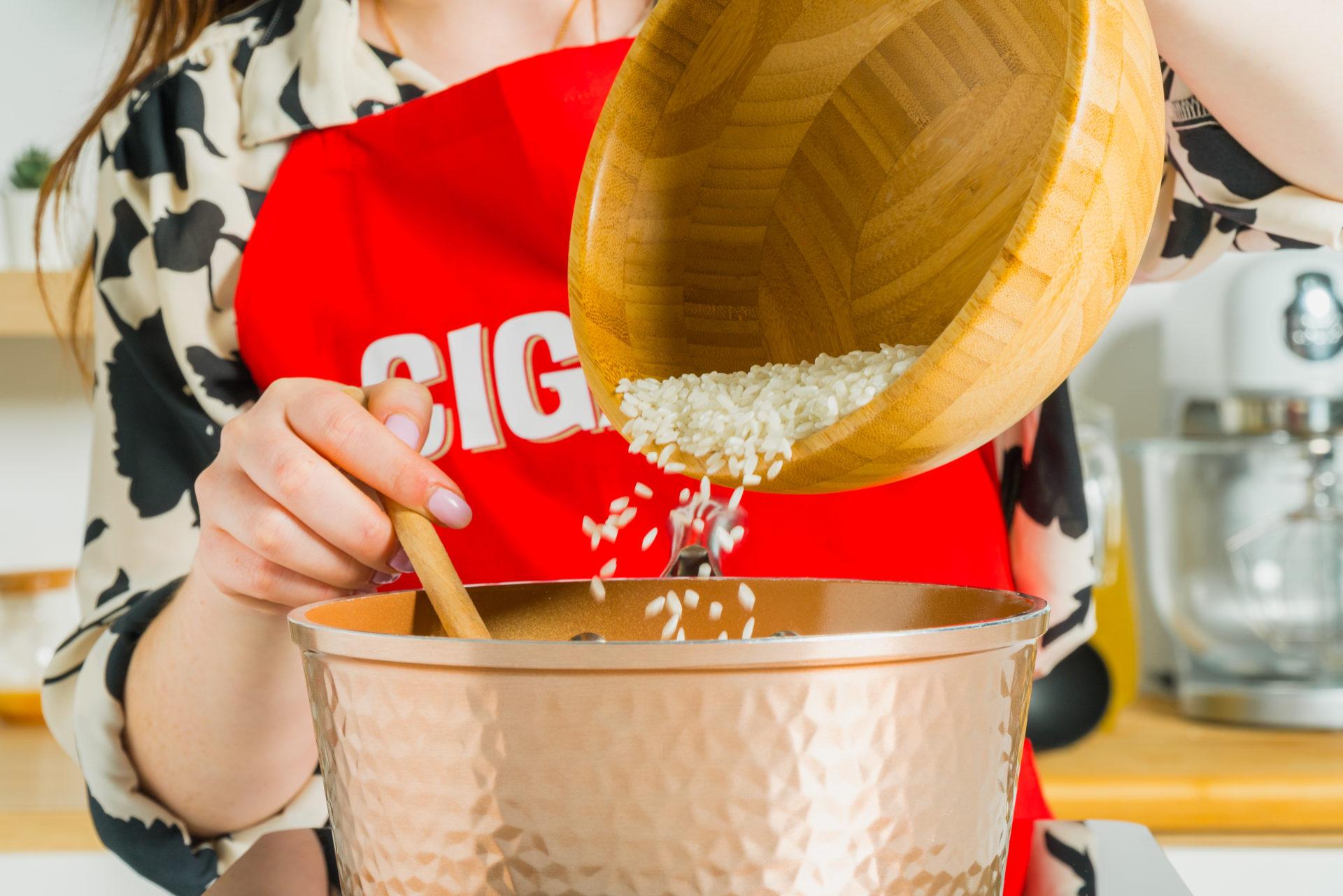 Pessoa a colocar arroz para dentro de uma panela