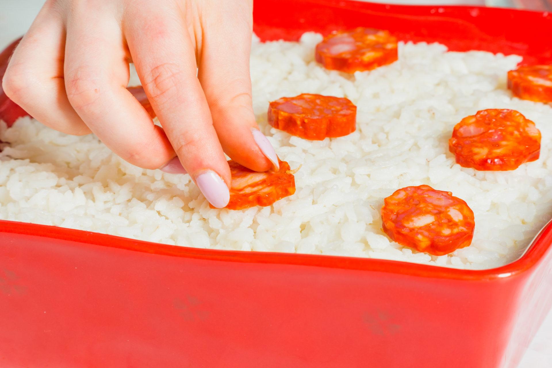Decorar o arroz com chouriça cortada às rodelas
